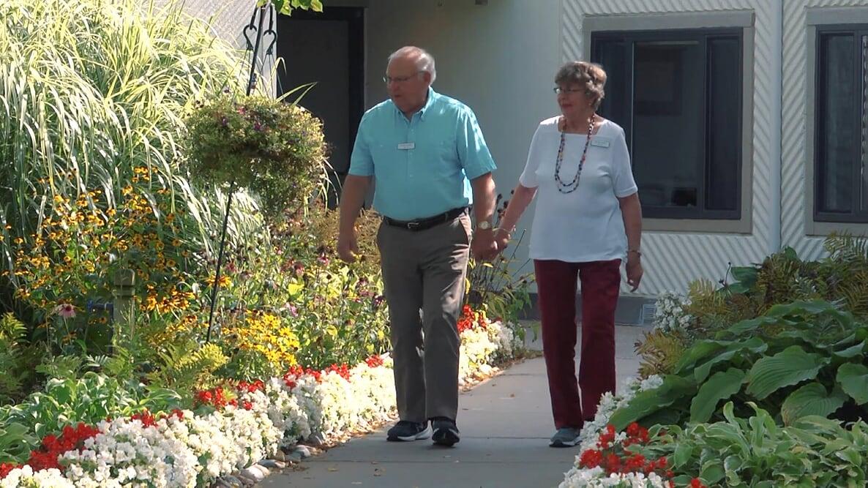 A senior couple pick flowers